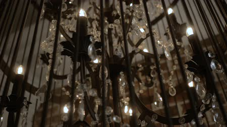 Chandelier in loft style on a black background. Chandelier on a black background, the object of luxury fashion. A chandelier in the shape of a bird cage