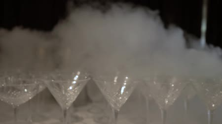 dioxid : Cold, white smoke spread along a row on the table, empty Martini glass. Leaving the camera from a large number of glasses shrouded in white smoke