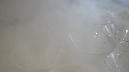 шампанское : Cold, white smoke spread along a row on the table, empty Martini glass