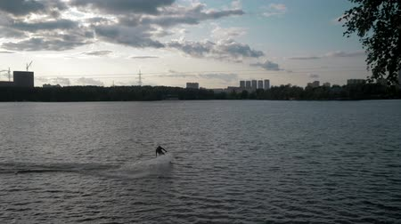 Wakeboarding on a Sunny summer evening. Wakeboarder passes in a static frame. Moving in and out of frame
