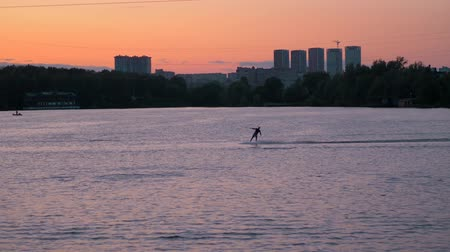Wakeboarding on a Sunny summer evening. Wakeboarding at sunset. Wakeboarder passes in a static frame. Moving in and out of frame Vídeos