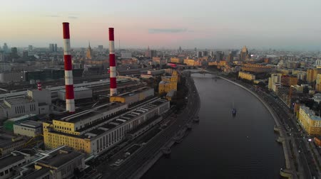 Aerial view of the city of Moscow and the Moscow river at sunset. Industrial pipes in the center of the megalopolis. 4K