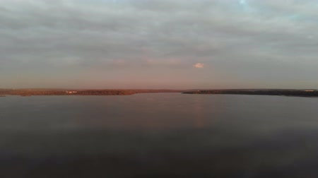 The camera flies over the lake at sunset. Shore in the distance, view from the sea. Aerial Vídeos