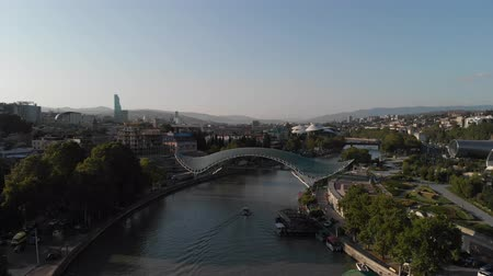 Aerial shooting of the city center of Tbilisi in Georgia. Peace Bridge. The camera flies a radius around the bridge