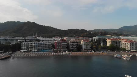 alpes : The coastline of the resort town. The camera shoots the beach of the resort town from the sea moving from right to left. Aerial view
