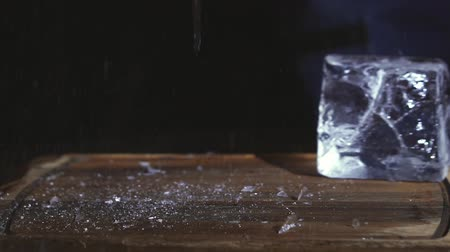 utensílio : Barman chopping ice using a special knife. ?hunks of ice flying around