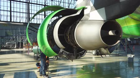 turbo : Engine and chassis of the passenger airplane under heavy maintenance. Engineer checks the aircraft engine. Stock Footage