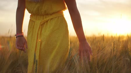walking back : A girl in a red dress runs across the field at sunset