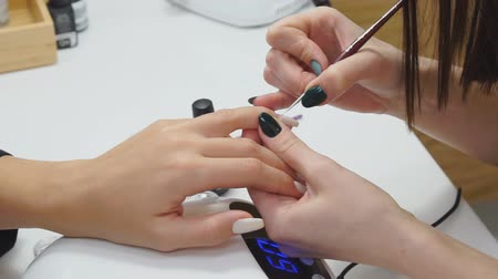 основа : Master of manicure makes a manicure on the nails of a woman. Close-up of beautiful female hands applying transparent nail polish on healthy natural womans nails in beauty salon.
