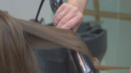 Hairdresser makes hairstyle close-up on blond hair of beautiful woman