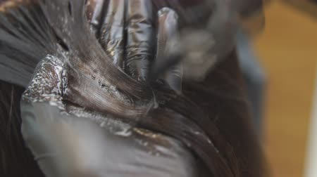 Close-up on the hands of the hairdresser. Master paints the hair of a girl in a beauty salon in black