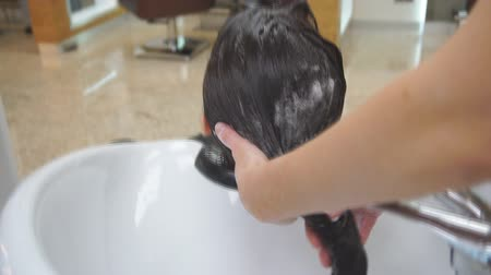 Close-up on the hands of the hairdresser. Master washes hair girl in a beauty salon in black.