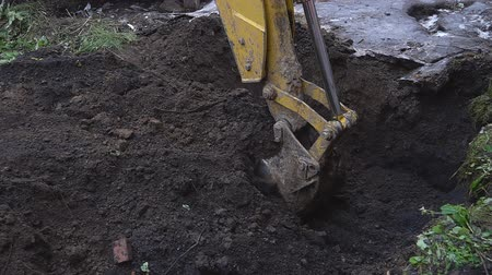 earthworks : Excavator shovel digs into a ground Stock Footage