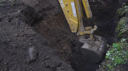 earthworks : Excavator shovel digging a deep hole