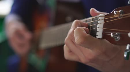 Mans hands playing acoustic guitar, close up