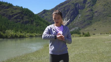 heart rate : Slow motion. Health sport young woman run and look wear smart watch device Stock Footage