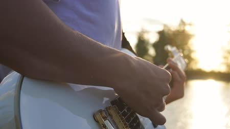 akkord : hands of guitarist playing electric guitar chords outdoors, evening, sunset