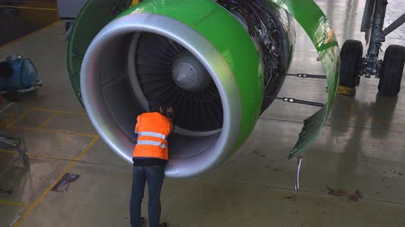 фюзеляж : Maintenance of aircraft. Repair of the tail of the aircraft. The engineer repairing the aircraft.. 4k