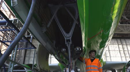 hangar : Engineer checks the operation of the hatch of the front landing gear of the aircraft