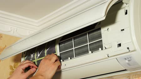 cleaning equipment : Man installs filters in air conditioner after cleaning