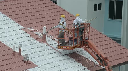 vállalkozó : Workers Painting The Roof Top Of A Building