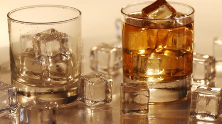 bourbon whisky : Pouring whiskey into the glass with ice which lies on the table Stock mozgókép