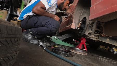 brake : Kajang, Malaysia - March 29th, 2019: Car mechanic replacing car wheel brake shoes of a lifted automobile at the repair service station. Stock Footage
