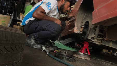 süspansiyon : Kajang, Malaysia - March 29th, 2019: Car mechanic replacing car wheel brake shoes of a lifted automobile at the repair service station. Stok Video