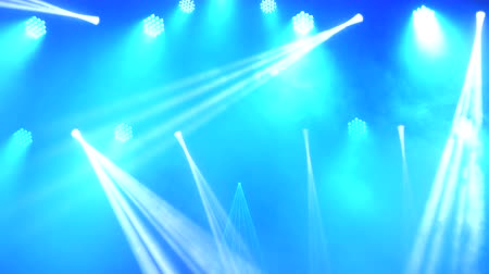 концерт : Bright flashing concert spotlights lasers and smoke at the scene background