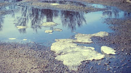 пробуждение : puddles and melted ice and snow at the sunny spring day