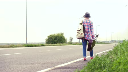 runaway : Young girl with a guitar coming along the road and hitch-hiking Stock Footage