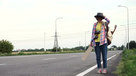 ukulele : Young girl with a guitar coming along the road and hitch-hiking Stock Footage