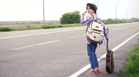 Young girl with a guitar coming along the road and hitch-hiking Stock Footage