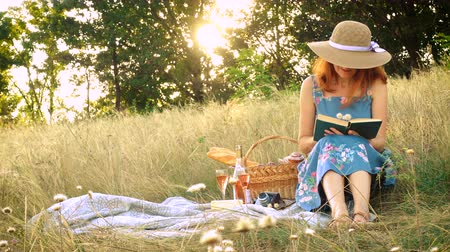 バゲット : girl with book on a picnic at the summer field