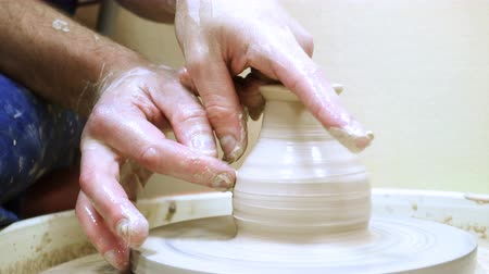 хозяин : Craftsman hands making a clay pot
