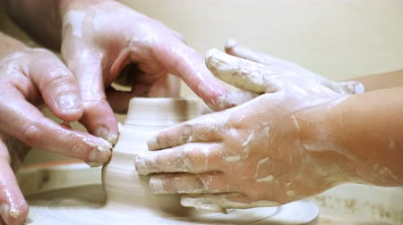 hands of adult man and child making a clay pot