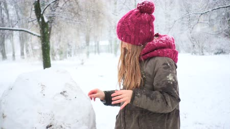 girl playing with snowman during snow fall