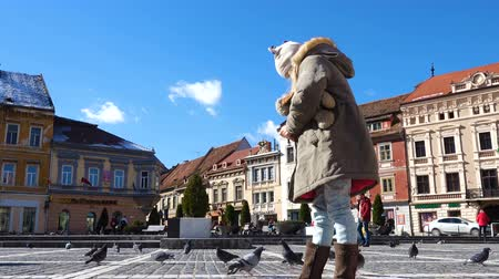 erdély : BRASOV, ROMANIA - NOVEMBER 01, 2017: child feeding pigeons on a main square of romanian town Brasov
