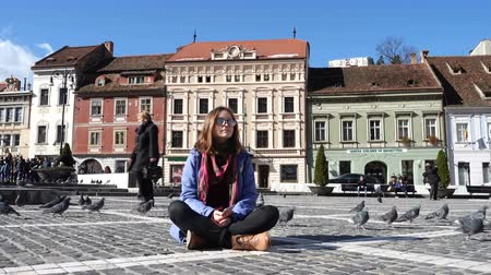 transilvânia : BRASOV, ROMANIA - NOVEMBER 01, 2017: teen girl sitting on a main square of romanian town Brasov Stock Footage