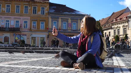 council of europe : BRASOV, ROMANIA - NOVEMBER 01, 2017: teen girl sitting on a main square of romanian town Brasov Stock Footage