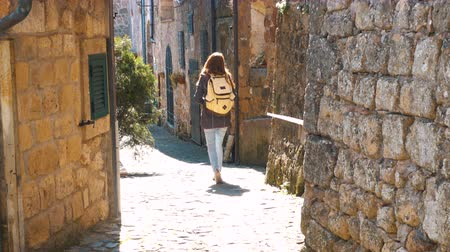 シエナ : young woman traveler walking on narrow streets of italian village