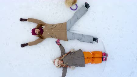 snow angel : top view of mother and daughter lying on a snow
