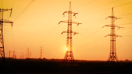 powerline : high voltage power lines at the field at the sunset time Stock Footage
