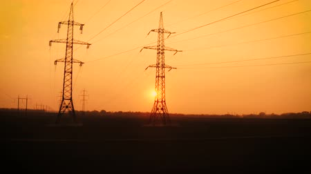 башни : high voltage power lines at the field at the sunset time Стоковые видеозаписи