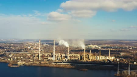 fuel and power generation : aerial view of smoke from the pipes of power plant station at the bank of a river