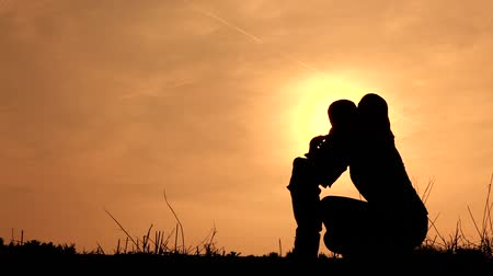 sunset : mum hugging her son silhouetted Stock Footage