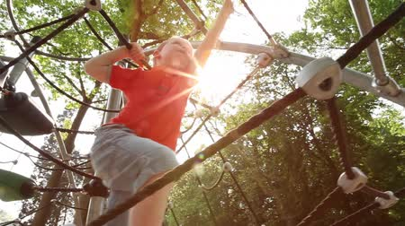 swing : boy achieves to climb across the rope