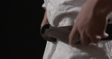 sztuki walki : judoka tightening black belt camera slide left