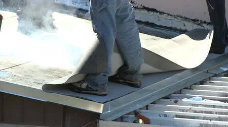 устанавливать : Roofers installing top layer on flat roof