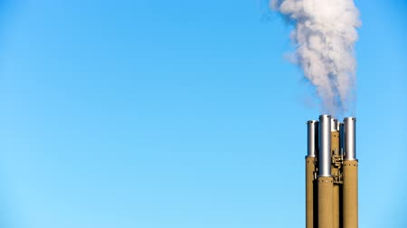 White smoke rising from smokestacks into the blue sky. Conceptual video of toxins like carbon, carbon dioxide and other polluting gases released into the atmosphere.